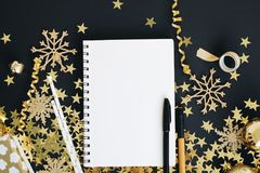 Christmas planning concept mock up. Notebook on black background with washi tape, gold stars confetti, gift, serpentine and glitte Stock Photography