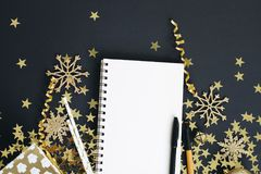 Christmas planning concept mock up. Notebook on black background with gold stars confetti, gift, serpentine and glitter snowflakes Royalty Free Stock Photography