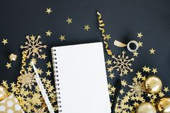 Christmas planning concept mock up. Notebook on black background with washi tape, gold stars confetti, gift, serpentine and glitte Stock Image