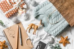 Christmas planning and shopping background. Blue knitted sweater in a paper bag, notepad, phone, christmas decoration on a light b. Ackground, top view royalty free stock photo