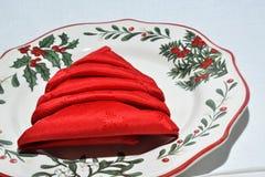 Christmas plate with folded napkin. A dinner plate with Christmas decorations and a red napkin folded like a Christmas tree Stock Image
