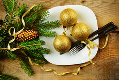 Christmas plate golden baubles pines wooden surface Stock Photo