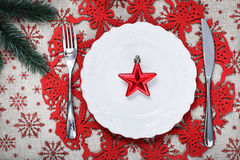 Christmas plate on holiday background with red star. Vintage Christmas plate on holiday background with red star. Canvas background with red glitter snowflakes Stock Photo