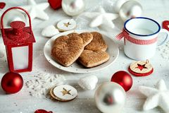 Christmas plate with homemade gingerbreads snowflakes baubles and lantern on a silver-plated table. Christmas plate with homemade gingerbreads snowflakes royalty free stock image