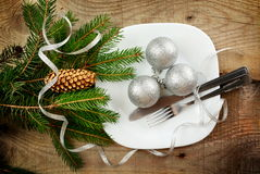 Christmas plate silver baubles pines wooden surface Royalty Free Stock Images