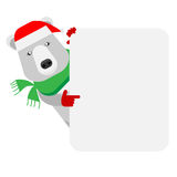 Christmas polar bear looks out of behind the wall Royalty Free Stock Images