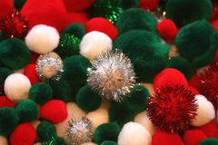 Christmas Pom Poms. Colorful red, green, and white Christmas pom poms used for crafts with a few sparkly ones stock image