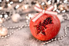 Christmas pomegranate on the table covered with snow. Selective focus stock photos