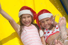Christmas by the pool. Two little girls on inflatable slide wearing christmas hats stock photos