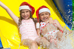 Christmas by the pool. Two little girls on inflatable slide wearing christmas hats royalty free stock photos