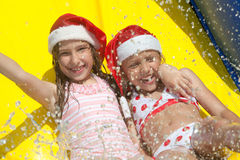 Christmas by the pool. Two little girls on inflatable slide wearing christmas hats stock images