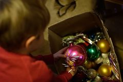 Christmas in a poor home. The child decorates the Christmas tree. royalty free stock photo