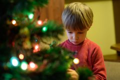 Christmas in a poor home. The child decorates the Christmas tree. royalty free stock photos
