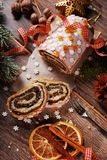 Christmas poppy cake on wooden table. Christmas poppy seed cake partly sleeced on wooden table in rustic style stock images