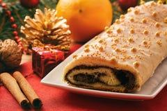 Christmas poppy seed roll cake on festive table. Royalty Free Stock Photos