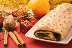 Christmas poppy seed roll cake on festive table. Stock Image