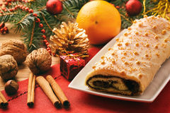 Christmas poppy seed roll on festive table. Stock Photos