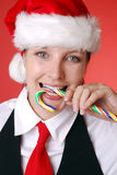 Christmas portrait. Young smiling woman with santa hat bites into a candy cane Royalty Free Stock Images