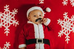 Christmas portrait of adorable newborn baby wearing Santa Claus` outfit royalty free stock photos