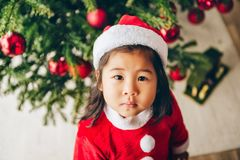 Christmas portrait of adorable 3 year old asian toddler girl wearing red Santa dress and hat. Sitting on the floor, top view stock images
