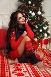 Christmas portrait of attractive woman with curly hairstyle. Beutiful brunette girl with long hair style wears in warm red knit royalty free stock photography