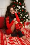 Christmas portrait of attractive woman with curly hairstyle. Beutiful brunette girl with long hair style wears in warm red knit royalty free stock photos
