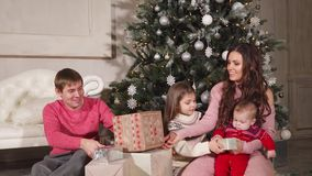 Christmas portrait of beautiful family. Portrait of a cheerful family of four sitting under the christmas tree. They are happily giving presents indoor stock footage