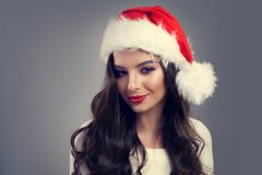 Christmas Portrait of Beautiful Smiling Woman in Red Santa Hat Stock Images