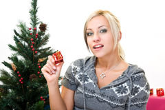 Christmas portrait of a beautiful young woman. Young woman holding a gift in a studio Stock Photography