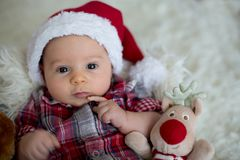Christmas portrait of cute little newborn baby boy, dressed in c stock photography