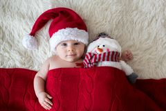Christmas portrait of cute little newborn baby boy, wearing santa hat. And hugging little cute snowman toy, studio shot, winter time stock photography