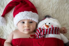Christmas portrait of cute little newborn baby boy, wearing sant Stock Photo