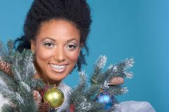 Christmas portrait of ethnic woman with black hair. Attractive female by decorated branches of Christmas tree Royalty Free Stock Image
