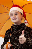 Christmas portrait of the girl 3. Christmas portrait of the girl in cap Santa Claus and with a umbrella Royalty Free Stock Photo