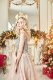 Christmas portrait of a girl in a glittering festive dress on the background of Christmas decor in elegant interior royalty free stock photo