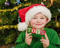 Christmas portrait of happy child wearing Santa hat in front of Christmas tree holding blocks Stock Images