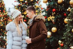 Christmas portrait of happy couple with hot mulled wine or tea walking on city streets decorated for holidays. Christmas trees with lights and toys on royalty free stock photography