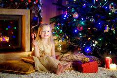Christmas portrait of happy little girl by a fireplace in a cozy dark living room Stock Image