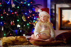 Christmas portrait of happy little girl by a fireplace in a cozy dark living room Stock Photos