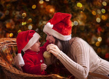 Christmas portrait. Portrait of happy mother and litle baby in santa's hats Royalty Free Stock Photography