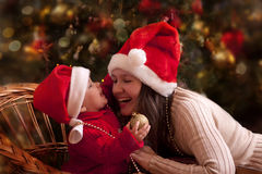 Christmas portrait. Portrait of happy mother and litle baby in santa's hats Stock Images
