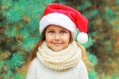 Christmas portrait happy smiling child little girl in santa red hat over tree Stock Photography