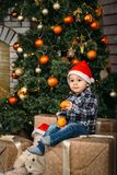 Christmas portrait of happy smiling little boy in red santa hat sitting on boxes with presents holding oranges in hands Royalty Free Stock Photography