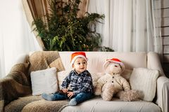 Christmas portrait of happy smiling little boy in red santa hat sitting on sofa playing with toy gun present. Royalty Free Stock Photography