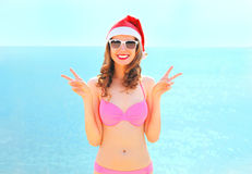 Christmas portrait pretty smiling woman in red santa hat on beach over sea background Stock Images