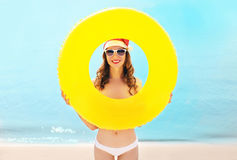 Christmas portrait pretty smiling woman in red santa hat with circle inflatable on beach over sea Royalty Free Stock Photo