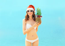 Christmas portrait pretty young smiling woman in red santa hat with pineapple on beach over sea Stock Photos