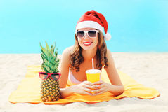 Christmas portrait pretty young smiling woman in red santa hat with pineapple cup fresh fruit juice lying on beach over blue sea. Background Stock Images