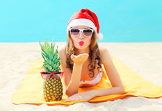 Christmas portrait pretty young woman in red santa hat with pineapple lying on beach sends air kiss over blue sea. Background Stock Image