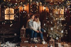 Christmas portrait of a romantic couple wooden hause royalty free stock photography